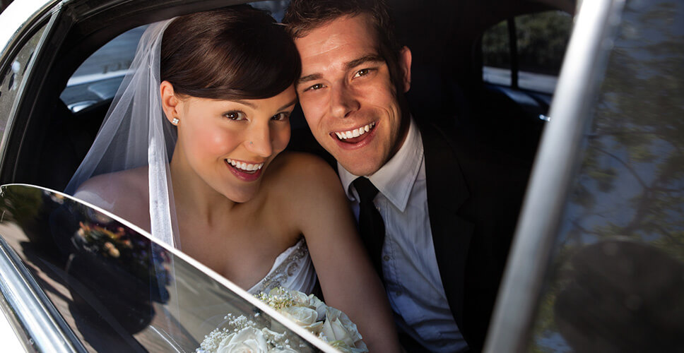Bride and Groom in the wedding limousine