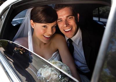 Bride and groom in wedding limousine
